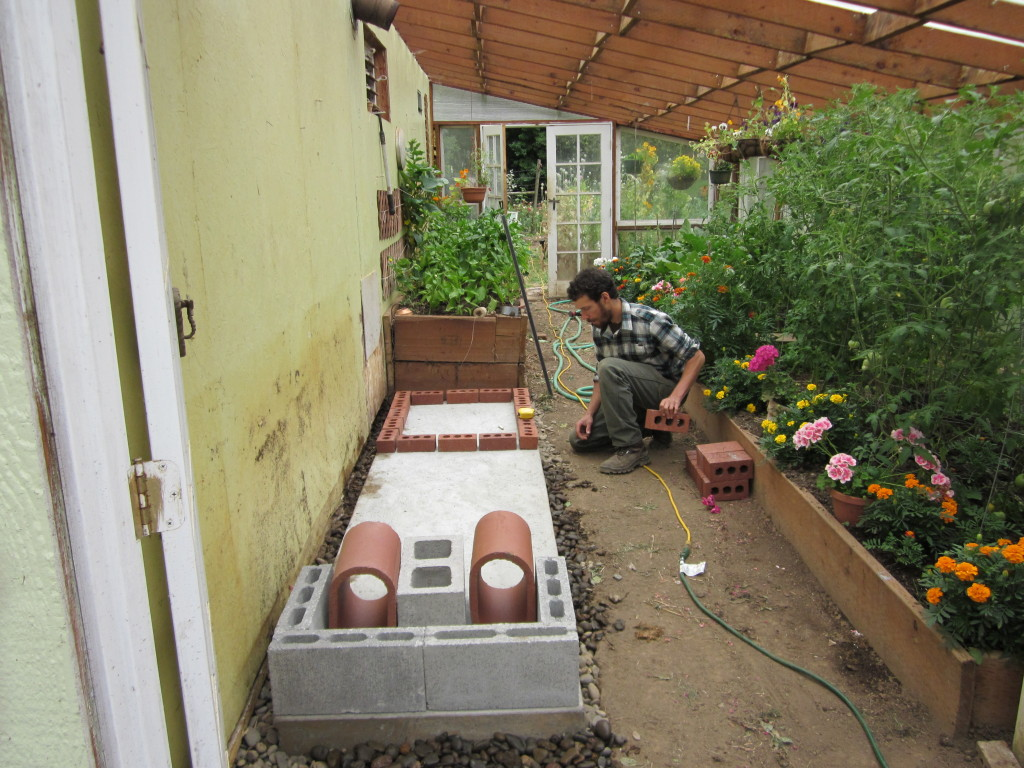 mass heater for a greenhouse using a wood stove hand print press