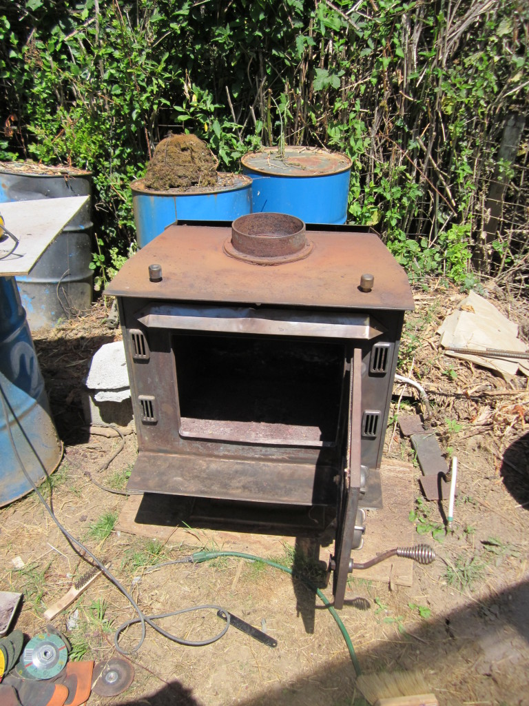 The original wood stove that inspired the project. Â I used a 4 1/2″  grinder with a metal cutting disk to cut out the baffle shelf it had inside. - Mass Heater For A Greenhouse Using A Wood Stove - Hand Print Press