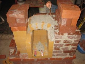 lasse's quick formless technique: one person holds the bricks in place while others fill the spaces w/chips and mortar